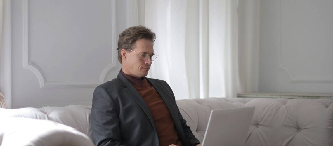 a-man-sitting-on-a-white-couch-using-laptop-3760378